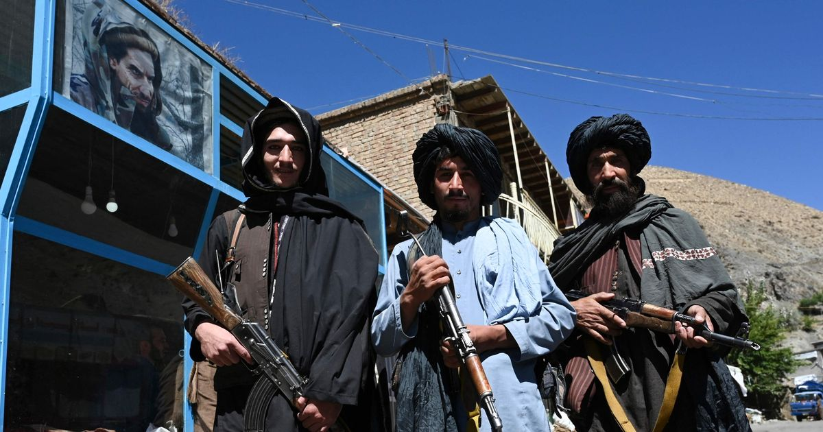Taliban fighters pose for a picture in front of a bakery