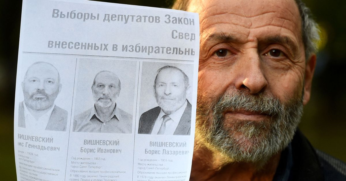 Boris Vishnevsky with a mockup of an official election poster featuring nearly identical photos of him and two other Boris Vishnevskys