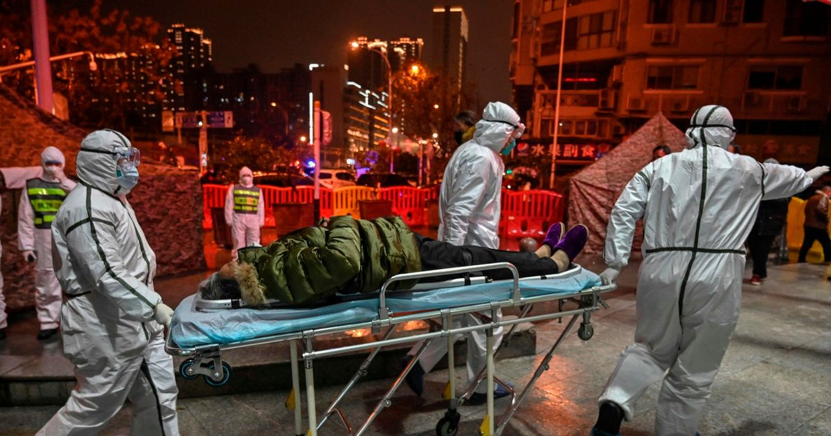 Medical staff members arrive with a patient at the Wuhan Red Cross Hospital in Wuhan