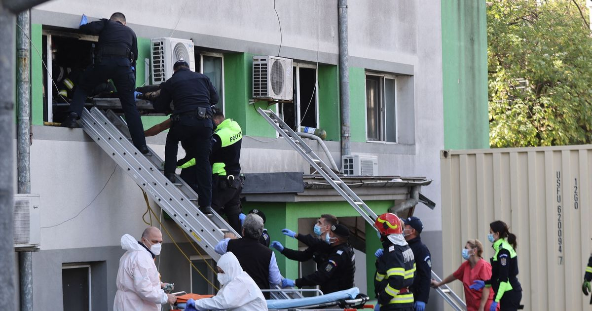 Firemen and policemen evacuate a burned victim from the infectious diseases hospital in Constanta, Romania