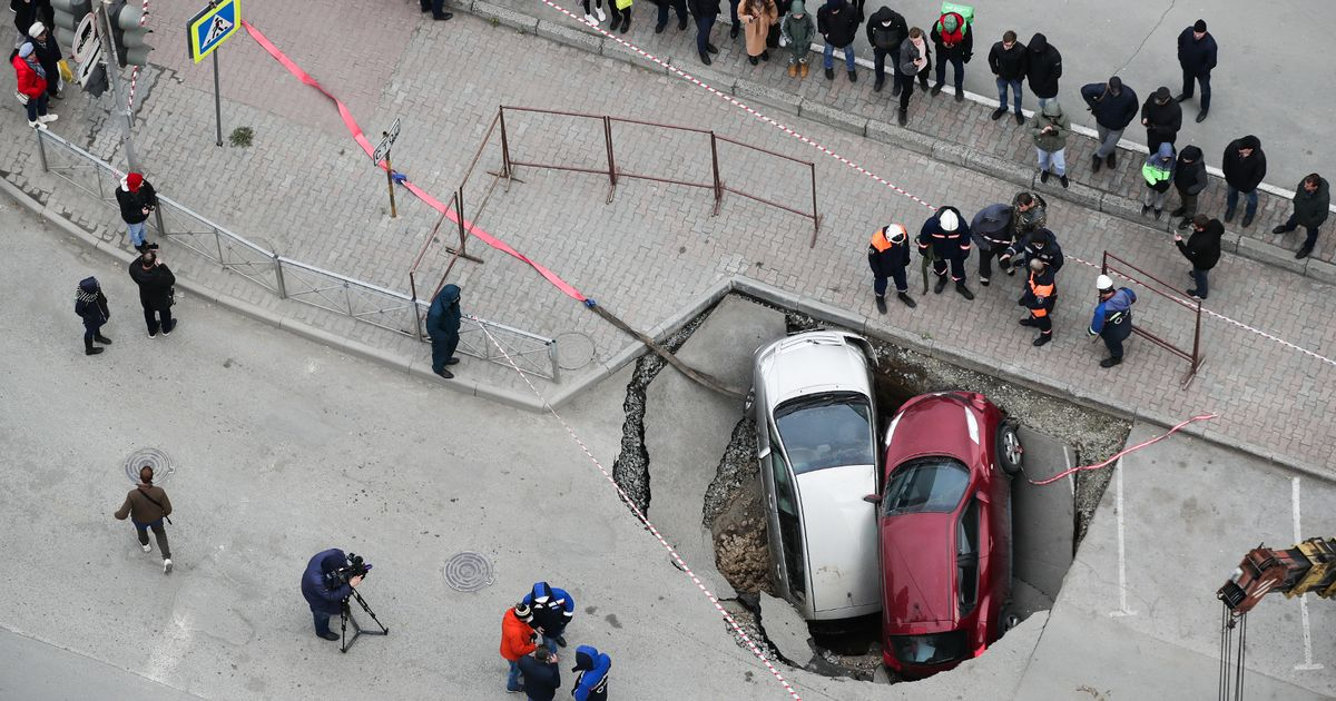 Sinkhole full of hot water swallows up two cars as crater suddenly opens at crossroads