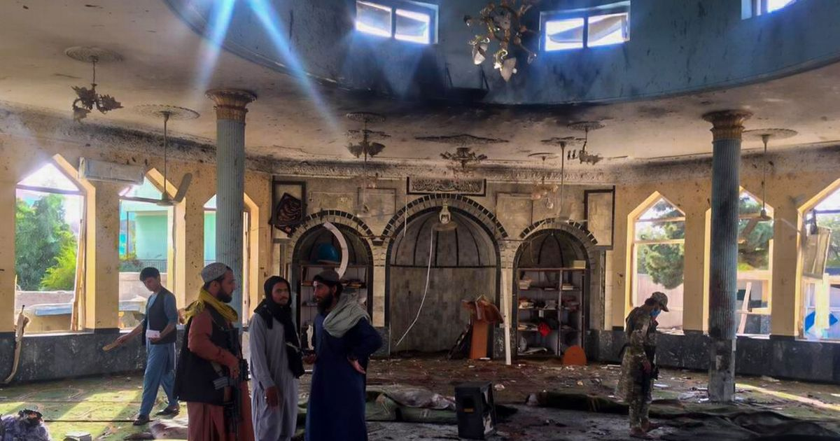 Men walk through a mosque ripped apart in a suicide bomb attack in a Shi