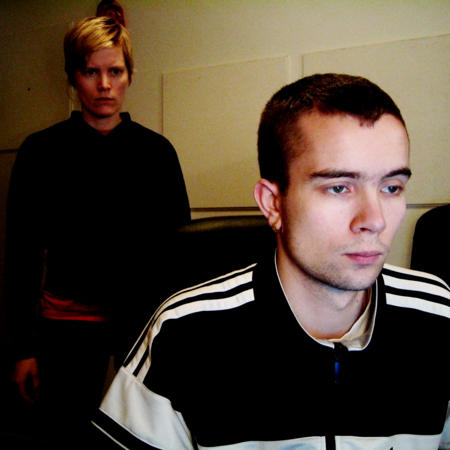 Karin standing behind Olof who is seated with his face ilumnated by a screen.