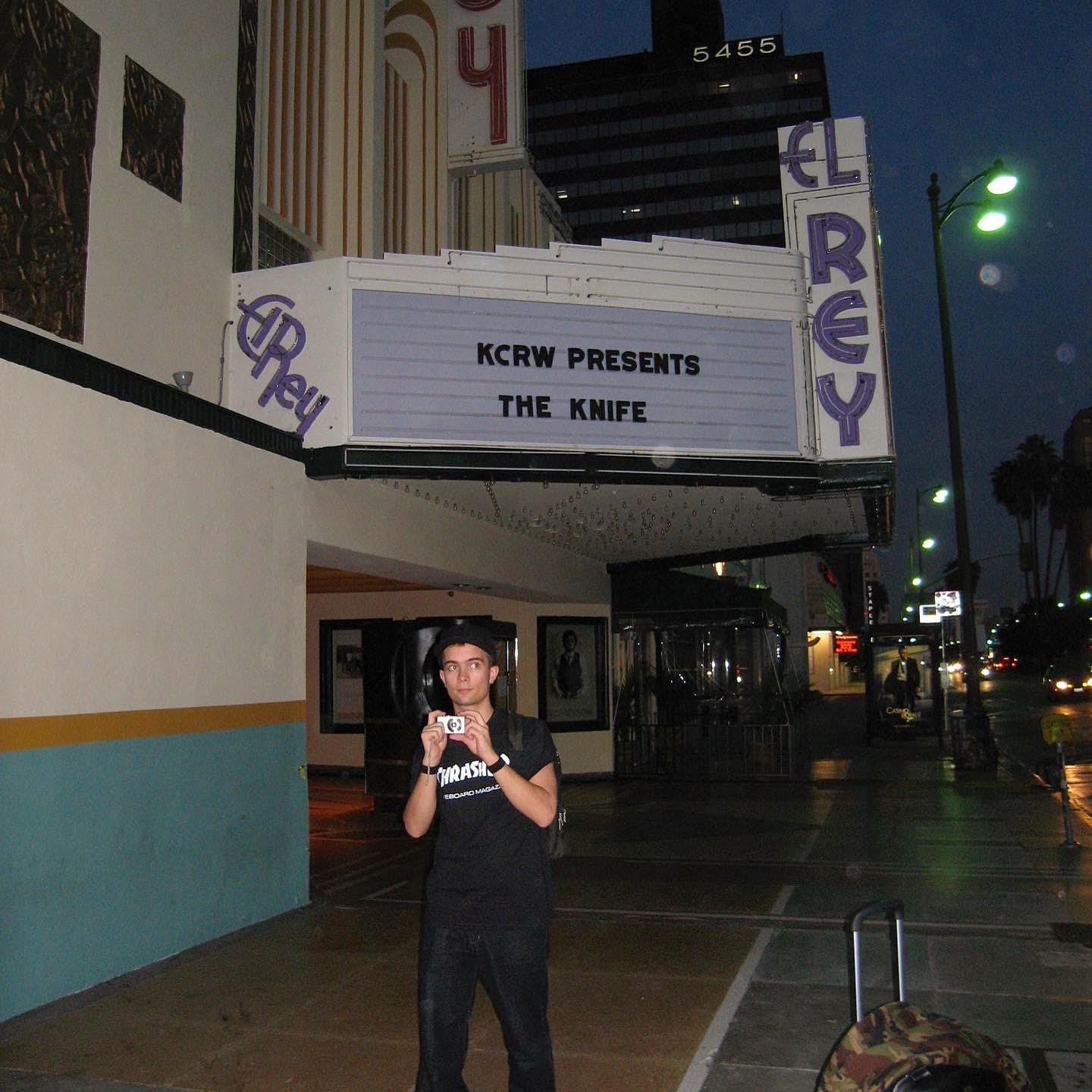 Olof pictured beneath the signage on the El Rey Theatre, LA, holding a point and shoot camera up to his chest, but looking off to the side.