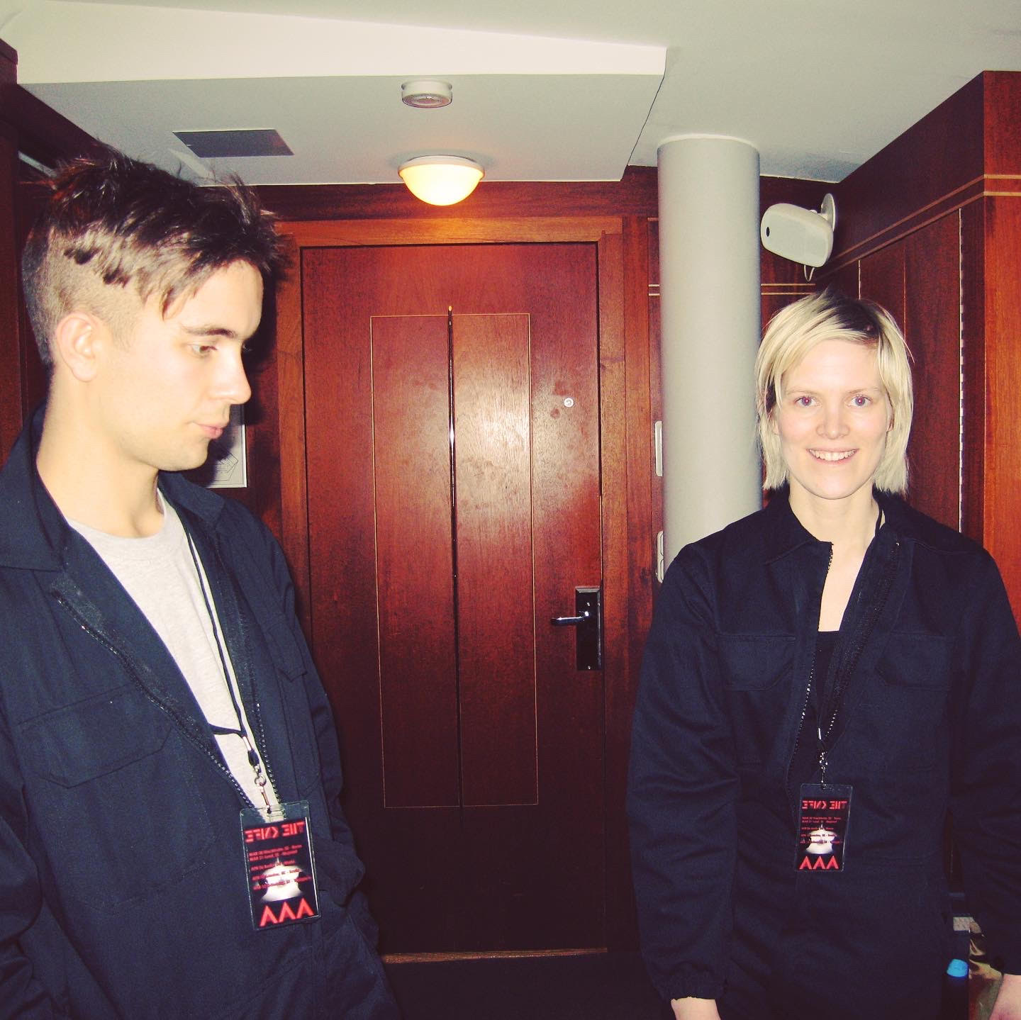 Olof standing side on and Karin facing the camera smiling, both dressed in dark blue boiler suits.