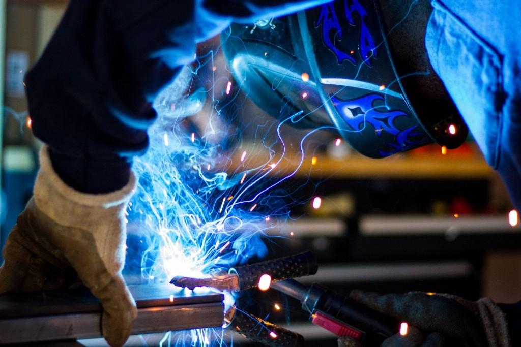 Blue sparks from a person wielding steel. Photo by Rob Lambert on Unsplash