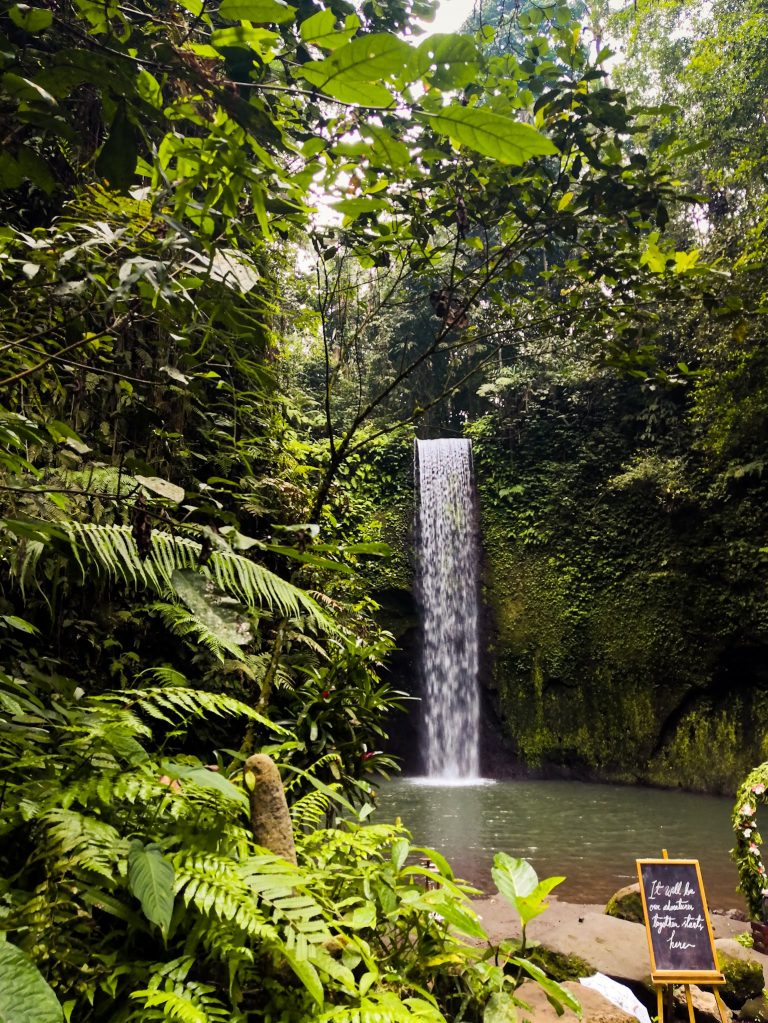 Tibumana waterfall and pool surrounded by jungle and cliffs