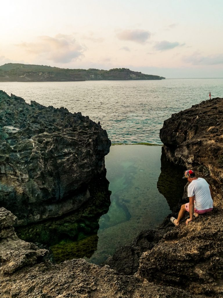 James sitting on the side rocks overlooking the crystal clear pool at Angel's Billabong