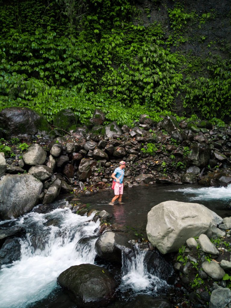 James crossing the shallow stream of water in between the viewing area and the fall