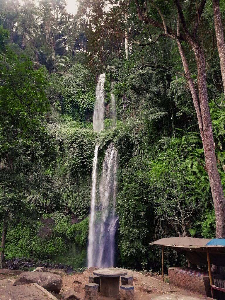 the two tiered Sendang Gile Waterfall with lush vegetation covering the cliffside