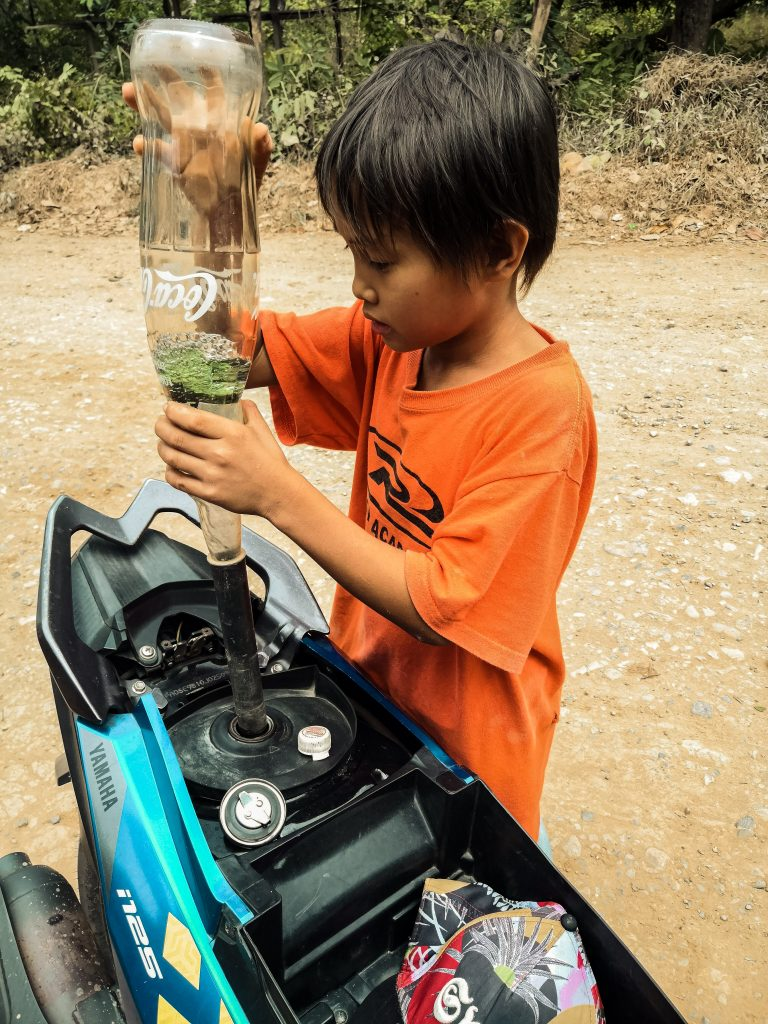 a Filipino kid fueling up our scooter