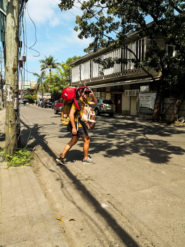 walking along the streets of Dumaguete and loaded with backpacks