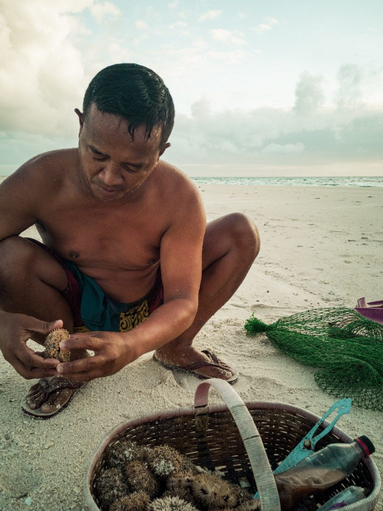 A Filipino fisherman cleaning a couple of sea urchins