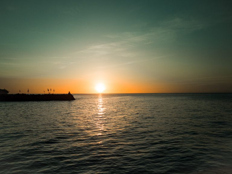 The sun slowly drowning in the distant ocean horizon on Camiguin at Medano Island Rest.