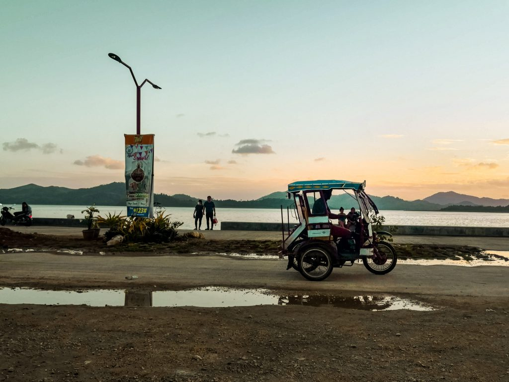 A tricycle waits along the coast in Dapa while the sun is slowly fading away behind the nearby islands in Siargao