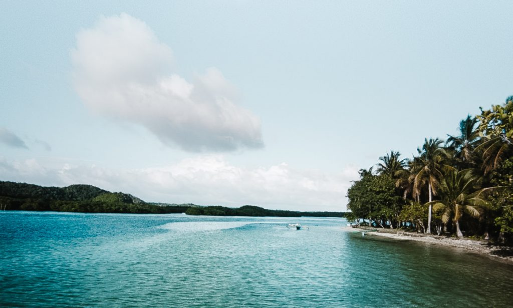 A view of Doot beach from the side including the blue sea and the beachfront covered in coconut trees