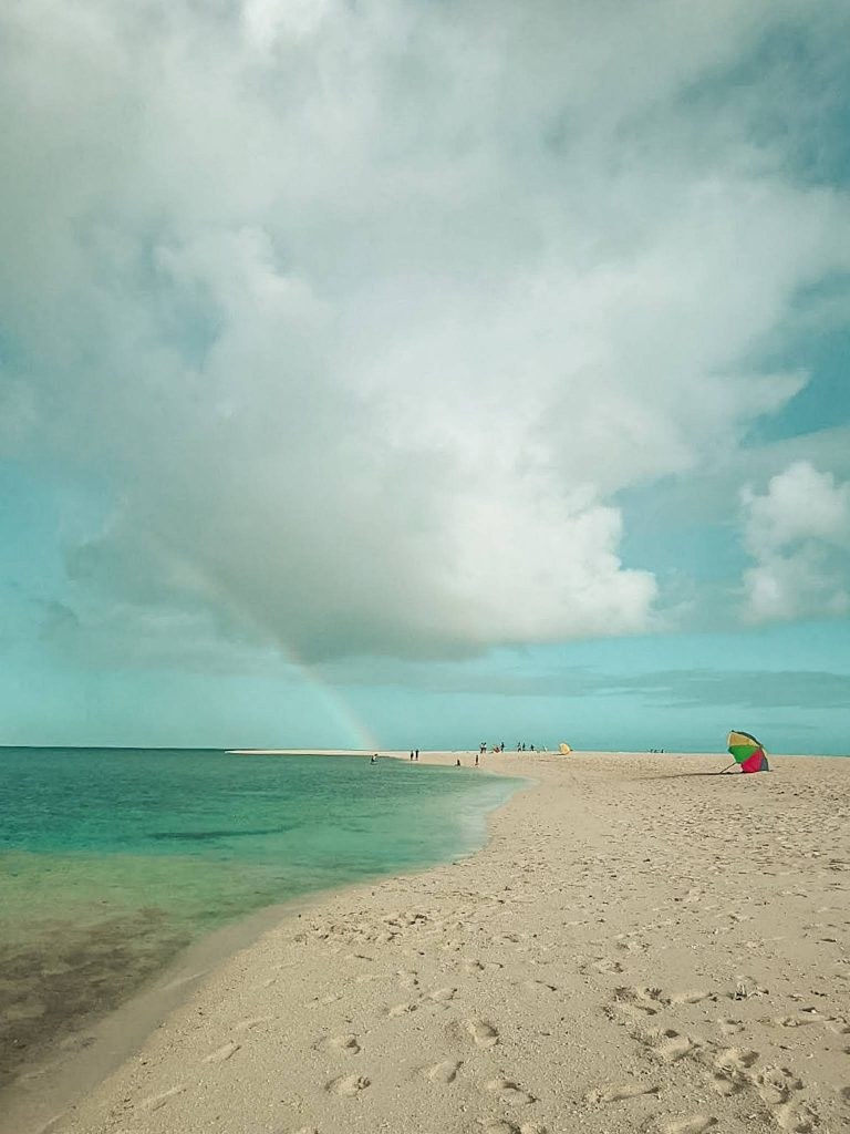 white sand, blue water at White Island and a rainbow further away
