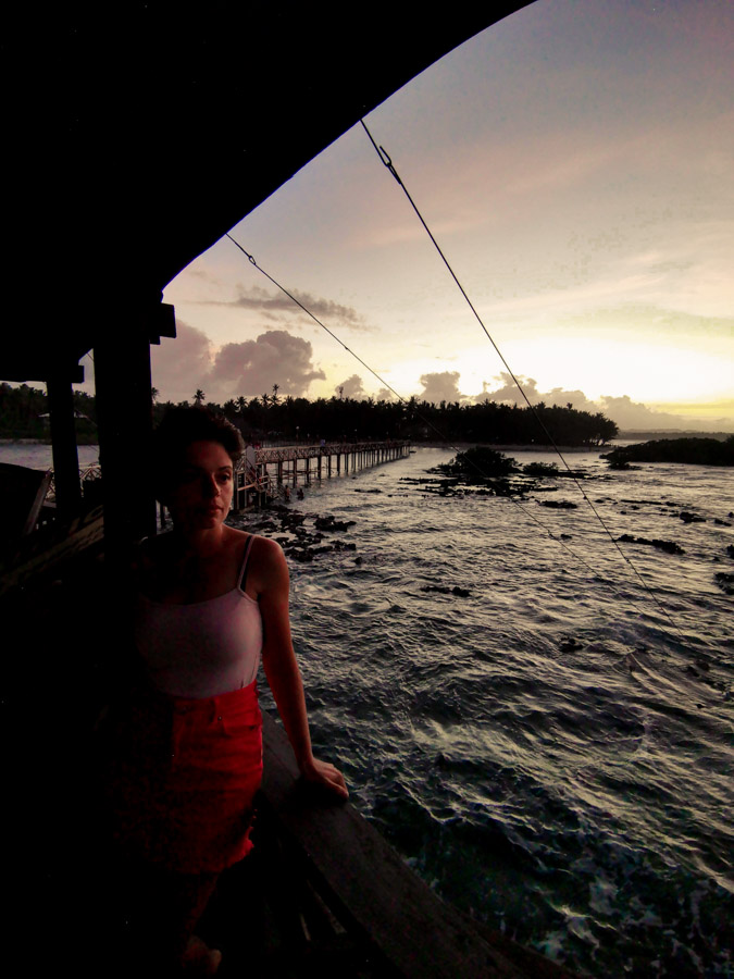 The sun setting from behind a cluster of palm trees from Cloud 9 boardwalk Siargao
