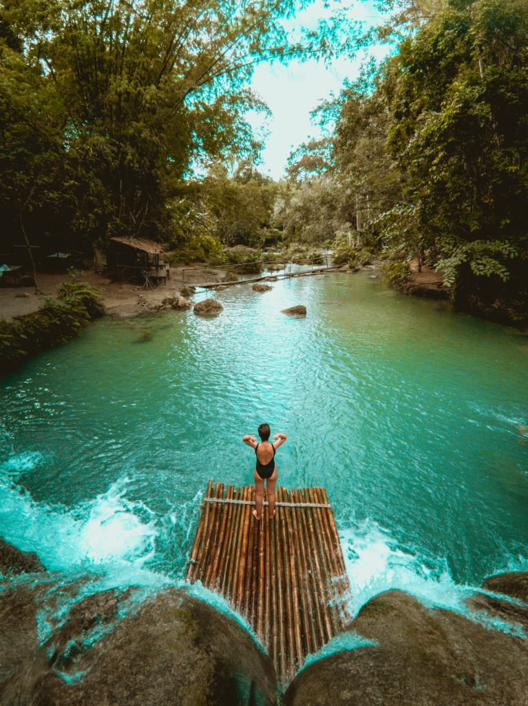Jacqueline posing on a bamboo raft at the foot of a waterfall cascading into a turquoise pool