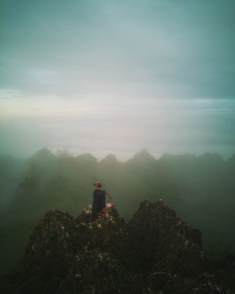 A silhouette of jagged rock formations peaking out into the foggy horizon at Osmena Peak