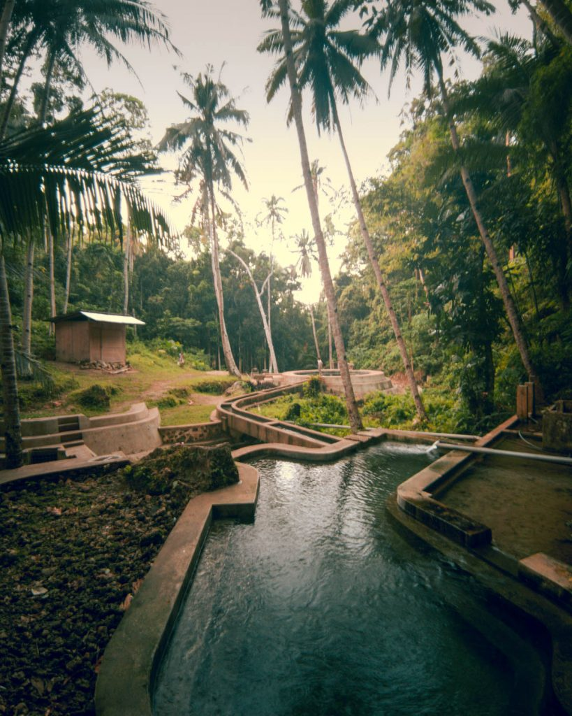Surrounded in huge coconut trees and a tropical landscape the man made water system and a big concrete pool contrast with their natural surrounding at Lugnason Falls