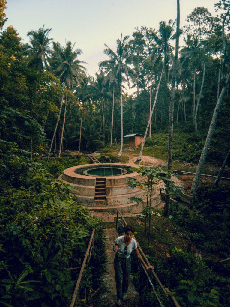 Surrounded in huge coconut trees and a tropical landscape the man made water system and a big concrete pool contrast with their natural surrounding