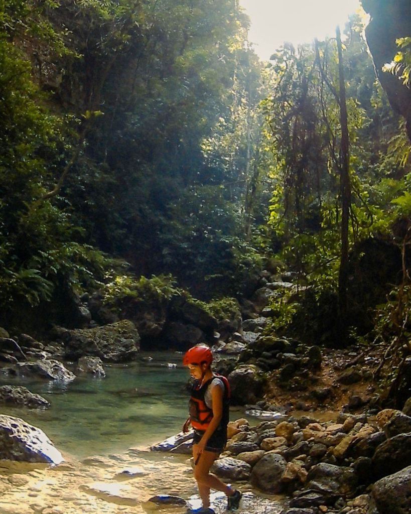 Surrounded in jungle and walking across a stream while canyoneering