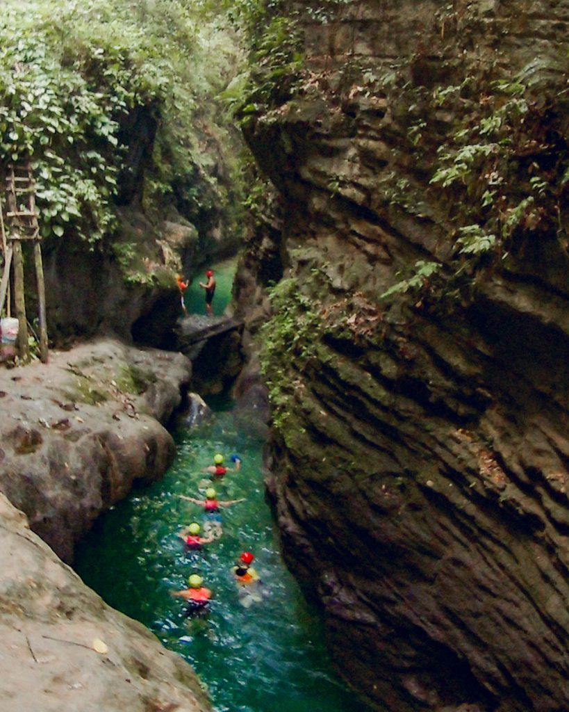 A turquoise river flows through a narrow canyon and above stalls selling food and drinks and there is one of the best cliff jumps