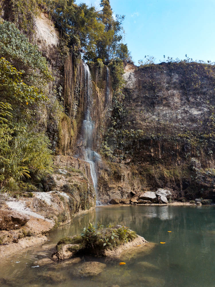 The cascade drops from high above the cliff