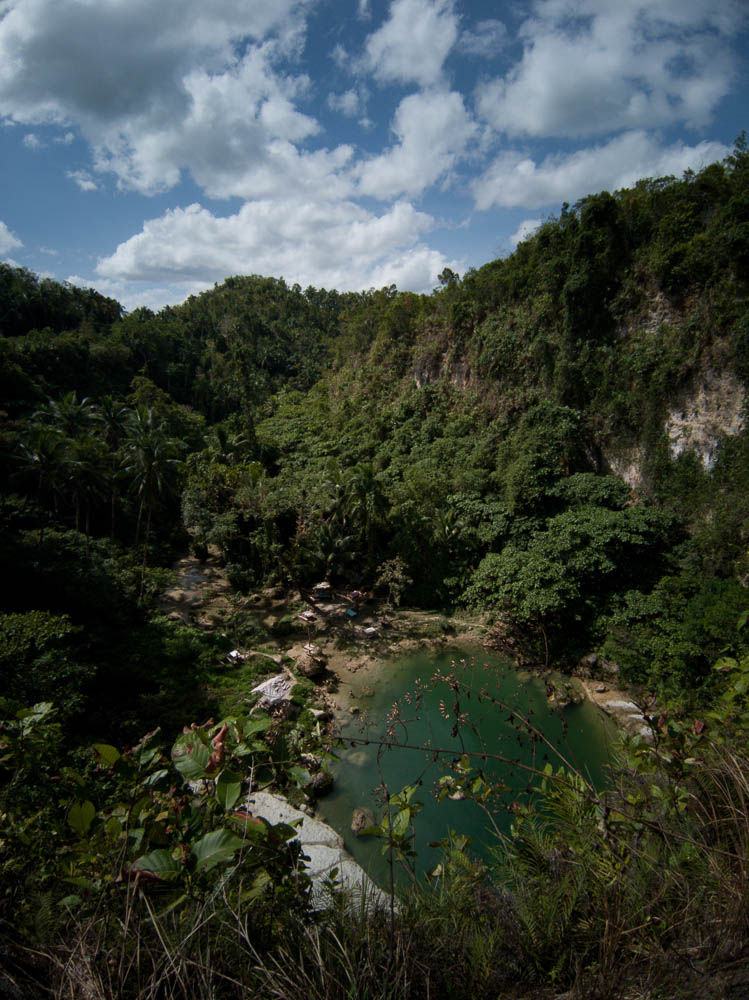 The vibrant blue pool at the end of a valley covered in jungle