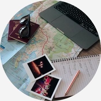 tools to use to plan travel; laptop, maps, notebook & pen