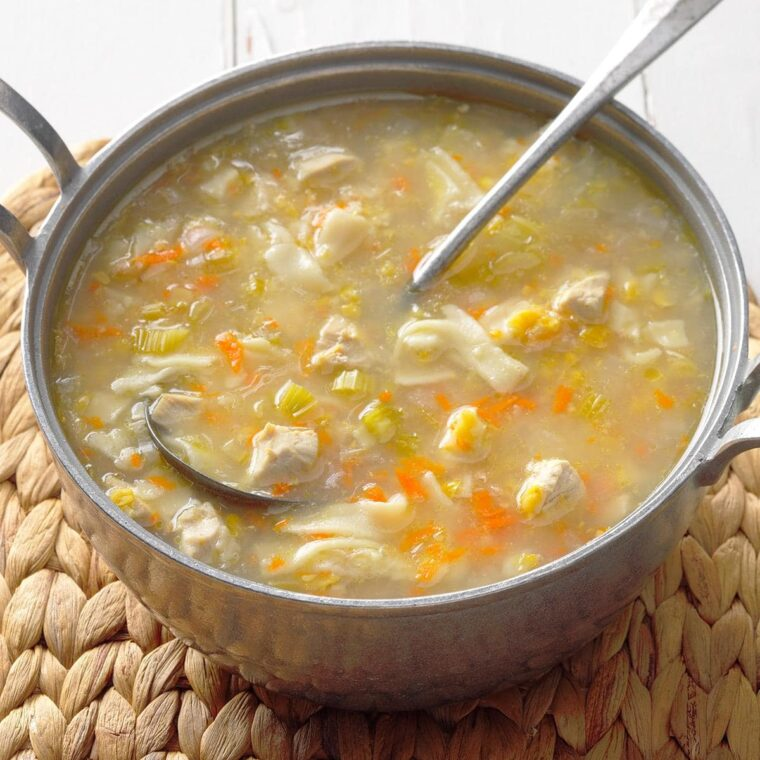 A bowl of soup and a spoon Description automatically generated