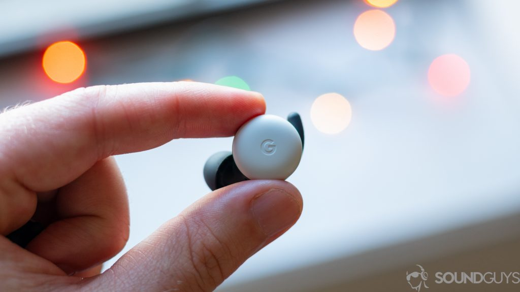 The Google Pixel Buds 2020 true wireless earbuds held in between an index finger and thumb.