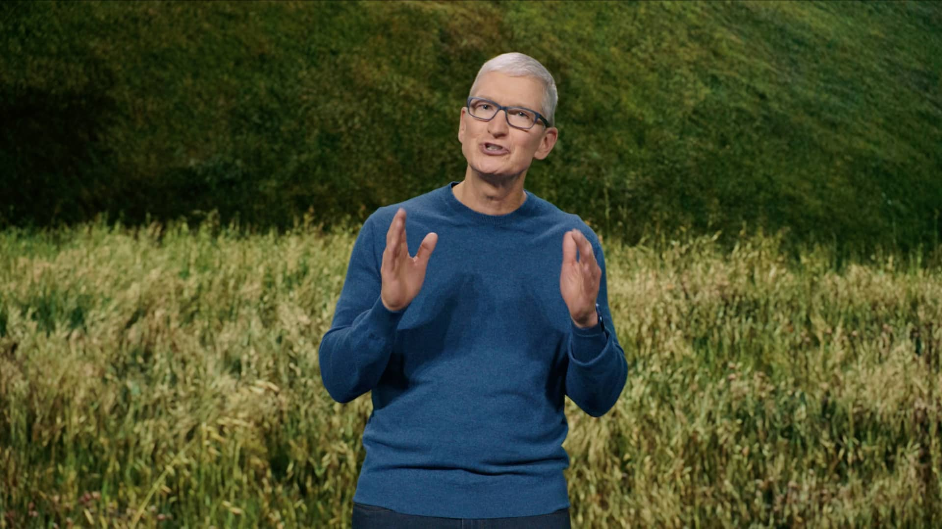 """A still image taken from Apple's September 2021 """"California Streaming"""" event video which shows CEO Tim Cook standing on stage and talking enthusiastically while gesturing with his hands"""