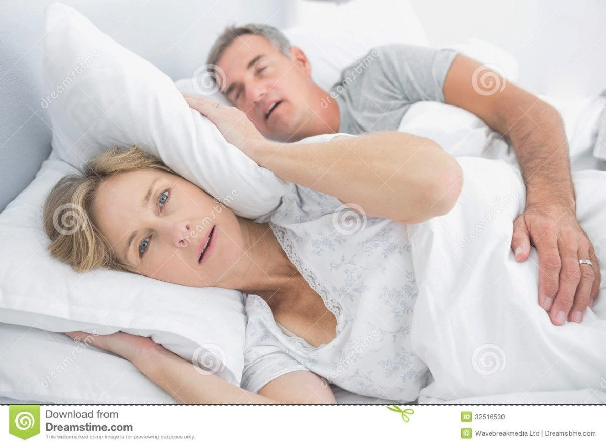 Irritated Wife Blocking Her Ears From Noise Of Husband in Husband And Wife In Bedroom