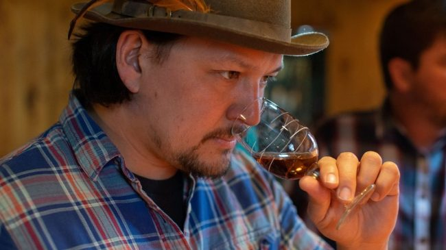 Smelling a glass of whiskey bourbon