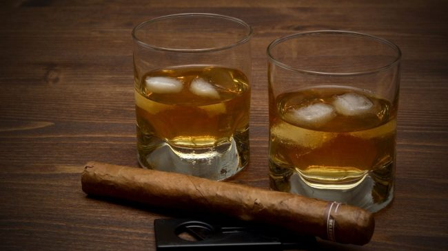 Whiskey on glass with ice and cigar