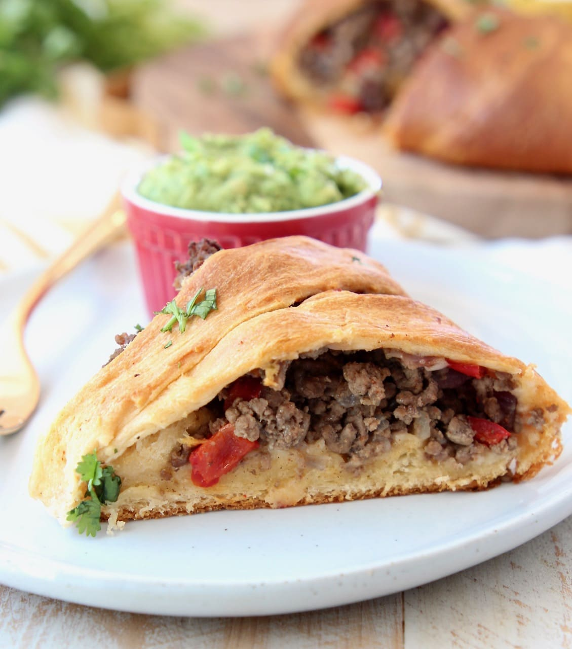 Slice of taco ring with crescent rolls filled with ground beef, with side ramekin of guacamole and gold fork