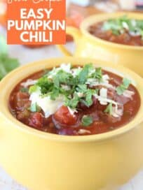 Pumpkin chili in yellow bowl topped with shredded cheese and cilantro