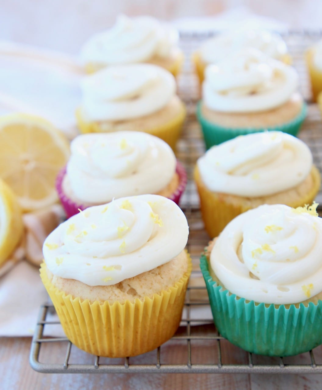 Lemon cupcakes with cream cheese frosting sitting on wire rack