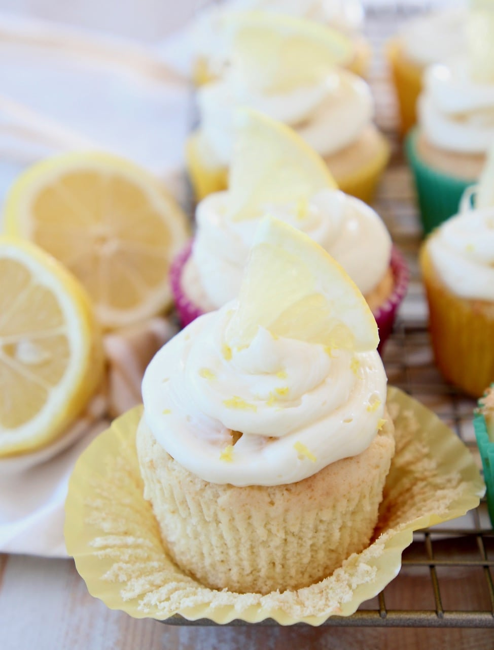 Lemon cupcake with wrapper unfolded, topped with lemon cream cheese frosting and lemon wedge