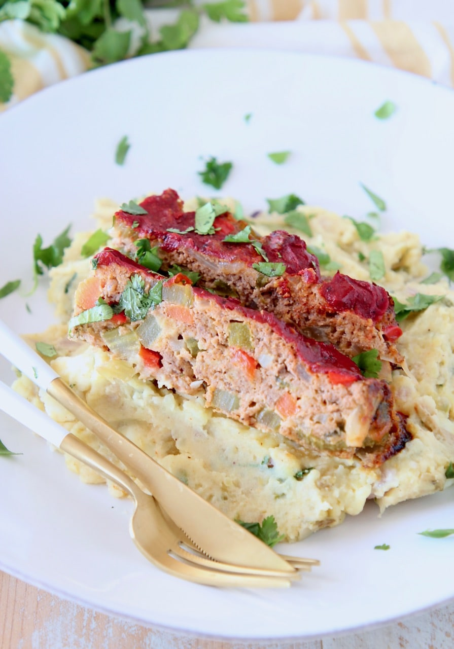 Two slices of Mexican meatloaf on top of mashed potatoes on plate with a gold fork and knife