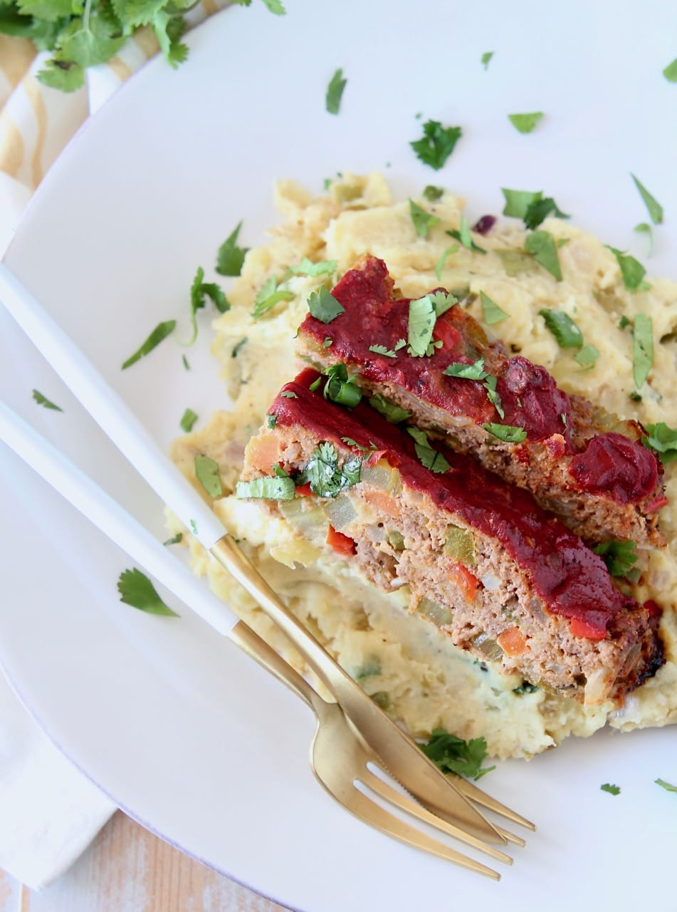 Two slices of Mexican meatloaf on top of mashed potatoes on white plate with fresh cilantro