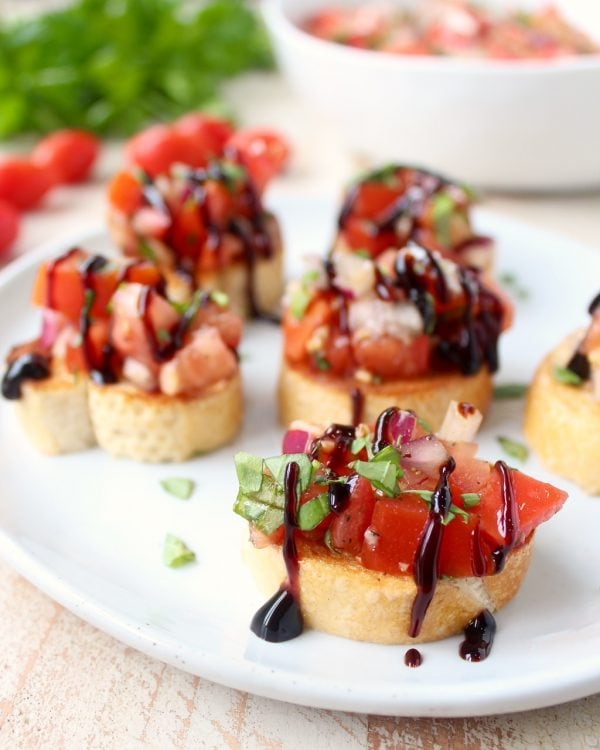 pieces of tomato bruschetta on plate drizzled with balsamic reduction