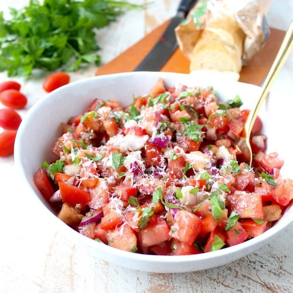 tomato basil bruschetta in bowl with gold spoon