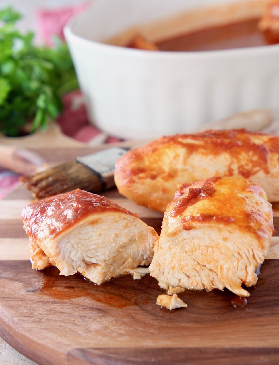Two pieces of baked chicken on wood cutting board with one piece of chicken sliced in half and pastry brush in the background