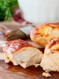 Baked Chicken covered in bbq and buffalo sauce, one piece sliced in half on wood cutting board with pastry brush in background