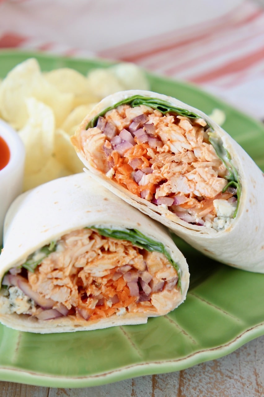 Buffalo chicken wrap cut in half and leaning on each other on green plate with potato chips