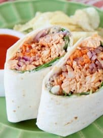 Buffalo chicken wrap, sliced in half, stood up next to each other on a green plate