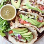Three ground beef tacos on wood tray with avocado and salsa